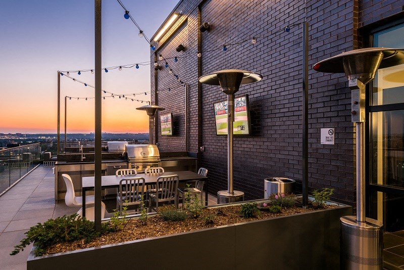 Rooftop seating area with entertainment and grill stations