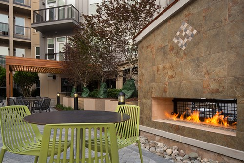 GATHER, Courtyard with outdoor fireplace and lush landscaping