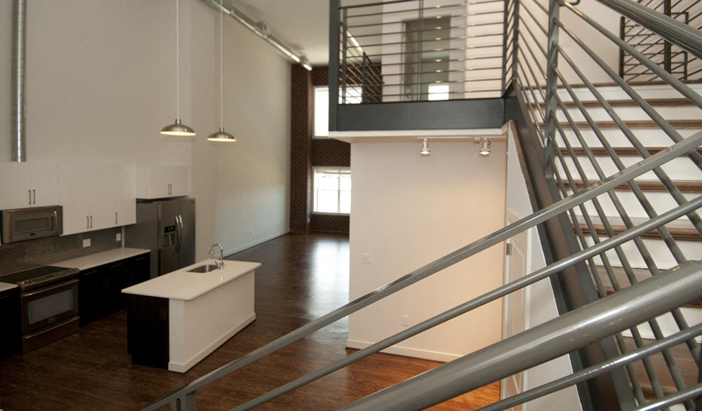 Unique two-story urban-style lofts with exposed ductwork and brick interior wall