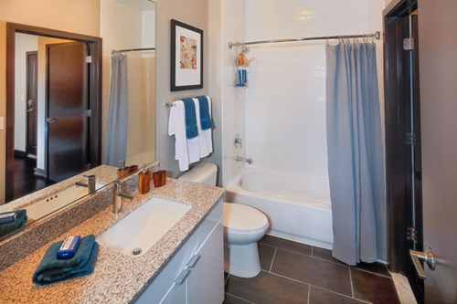 Expansive bathroom with spacious granite counters and subway-tile