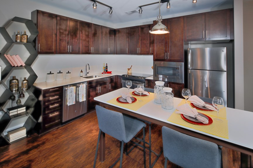 Kitchen with premium cabinetry, under-cabinet lighting, granite counters, islands and stainless steel appliances