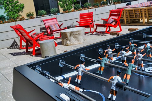 GATHER courtyard with outdoor seating grilling stations and foosball