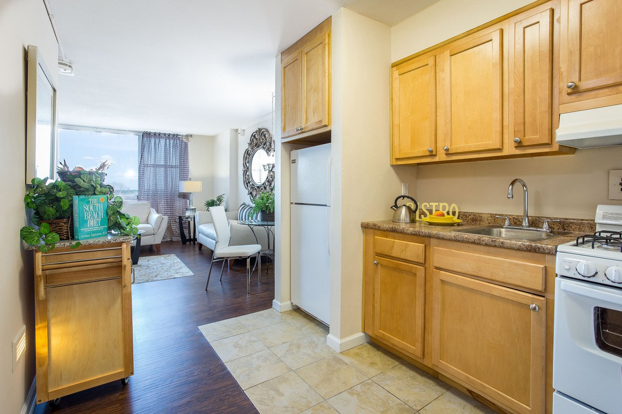 Kitchen equipped with granite counter tops and white appliances. opens into living room.