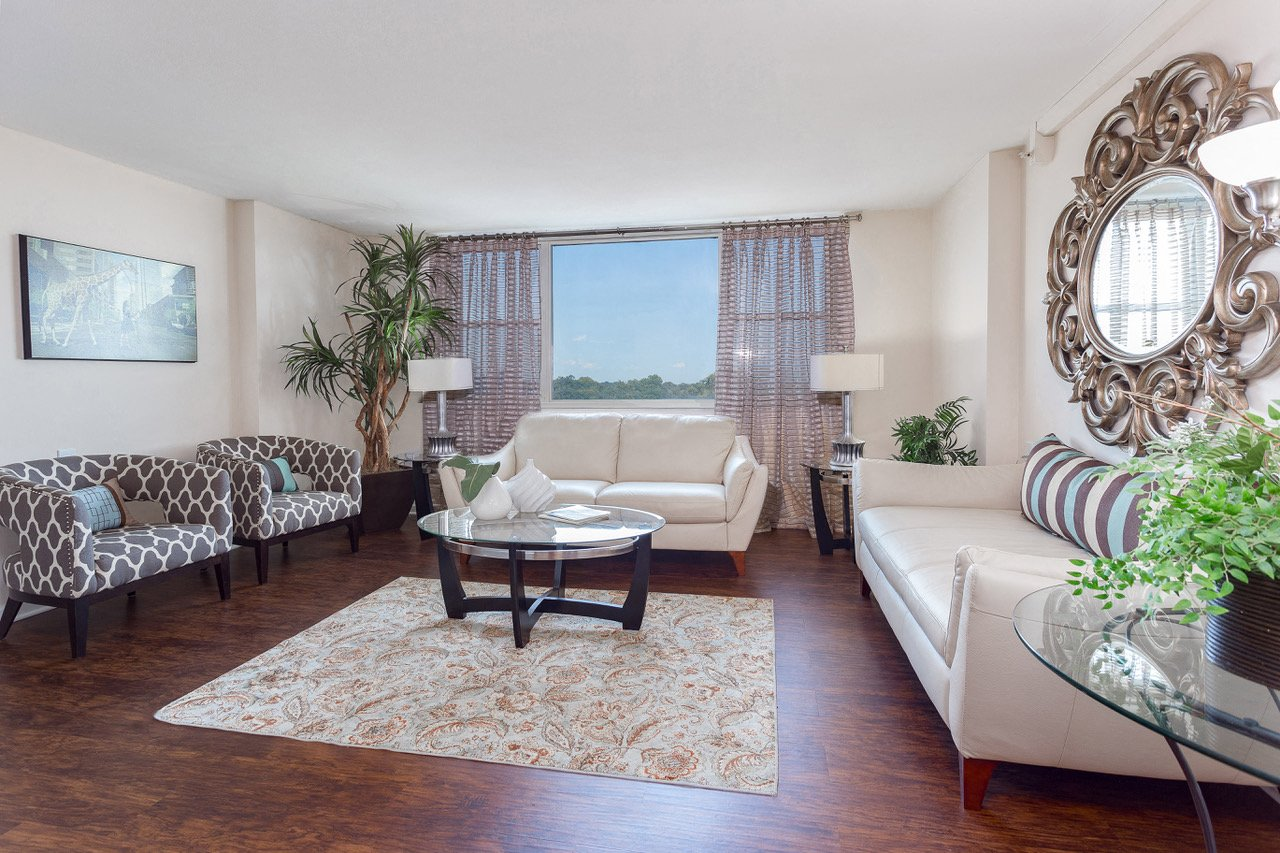 Furnished model living room with light beige walls, wood flooring, and three windows.