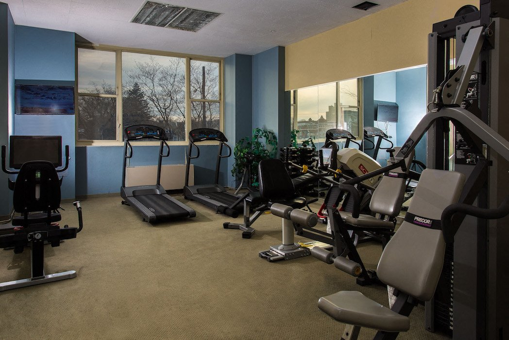 Exercise room equipped with treadmills, indoor bikes, weight machines, and a television set.