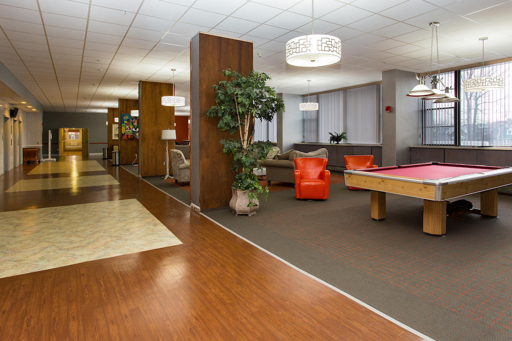 Lounge with pool table, seating, and a large television set.