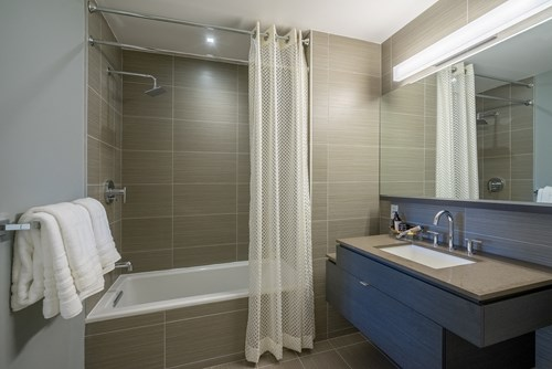 Brushed Nickle Fixtures and Custom, Wall-Tiled Bathrooms