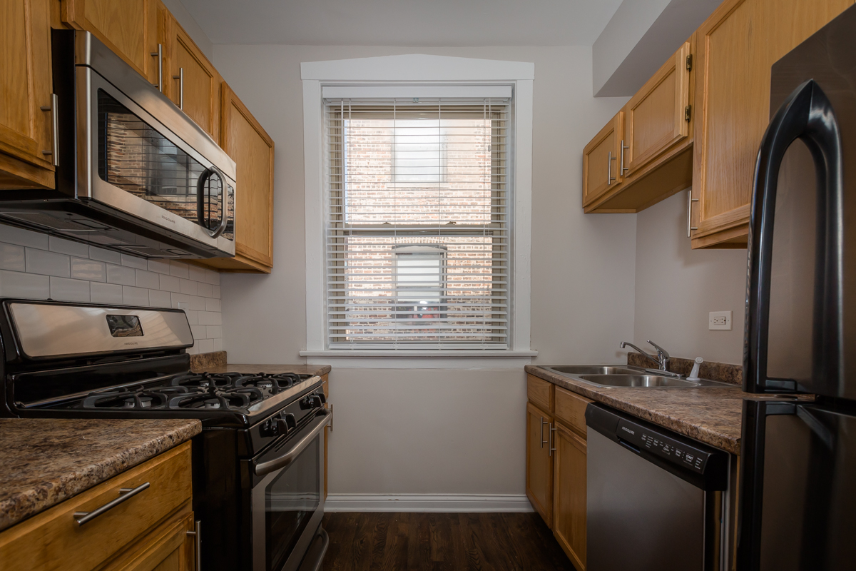 renovated kitchen stainless steel appliances wood floors hyde park chicago apartment rental